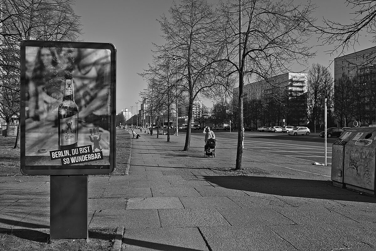 Street view of the Karl-Marx-Allee in Berlin, with an advertisement billboard