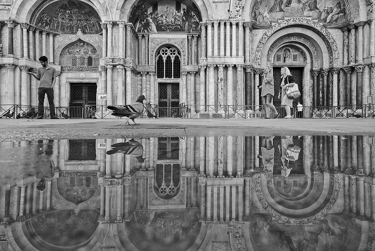 The facade of the Basilica of St. Mark reflected in the tidal water on the square