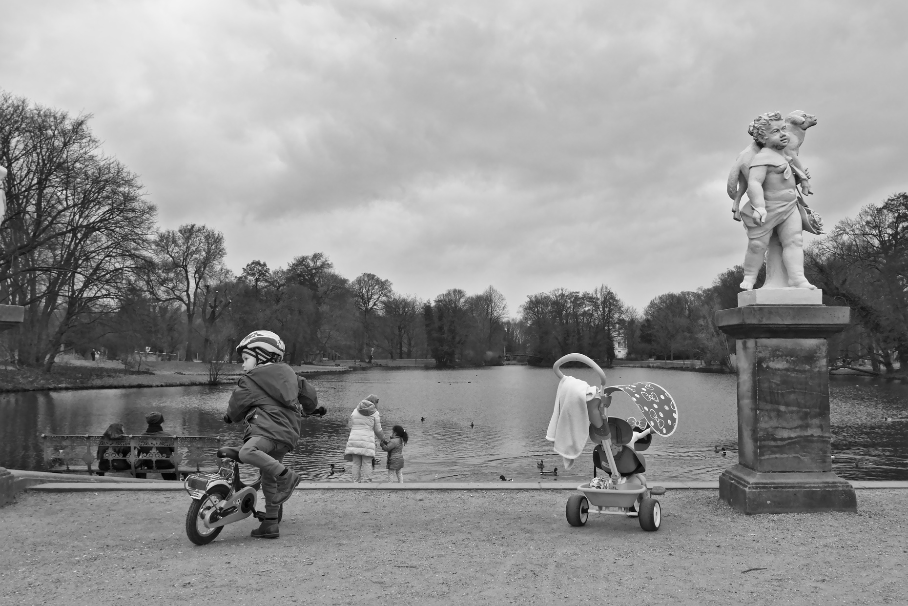 A young boy unmounting his bicycle in the garden of Schloss Charlottenburg