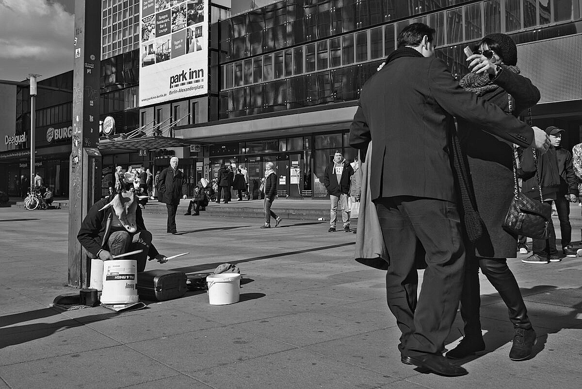 A couple is greeting heartily in Alexanderplatz in Berlin, with a street musician wearing a giraffe head playing drums on buckets