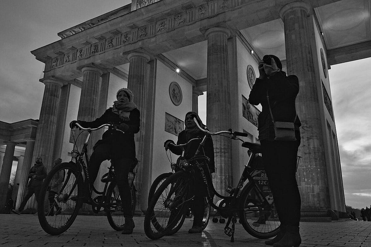 Three women on bicycles at the Brandenburger Tor in Berlin, around sunset.