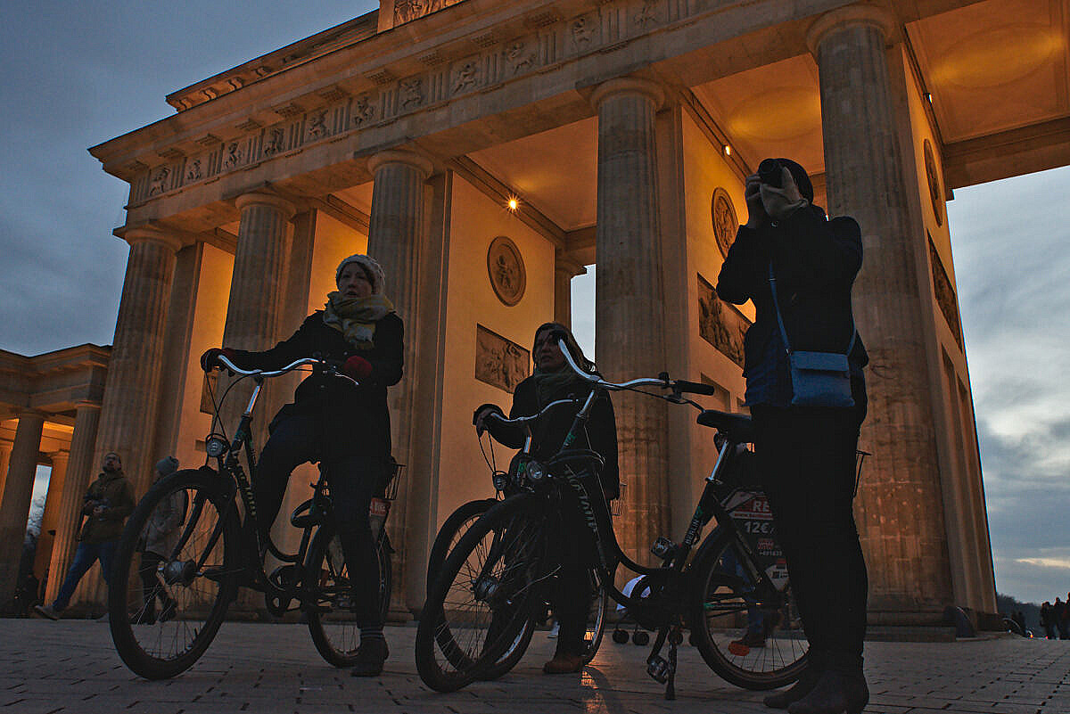 Three women on bicycles at the Brandenburger Tor in Berlin, around sunset.