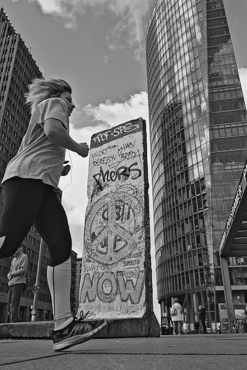 Girl running over the Potzdamer Platz in front of a piece of the Berlin wall