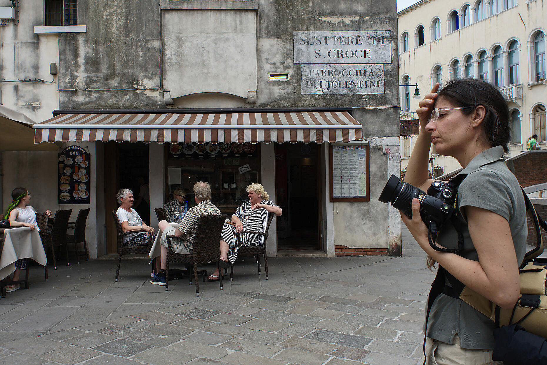 Tired female photographer in front of a bar full of tourists in Venice.