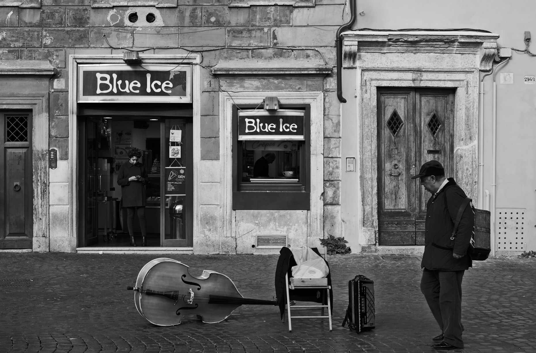 An ice cream parlour in Trastevere in Rome, with musical instruments abandoned one the road and another street musician walking past.