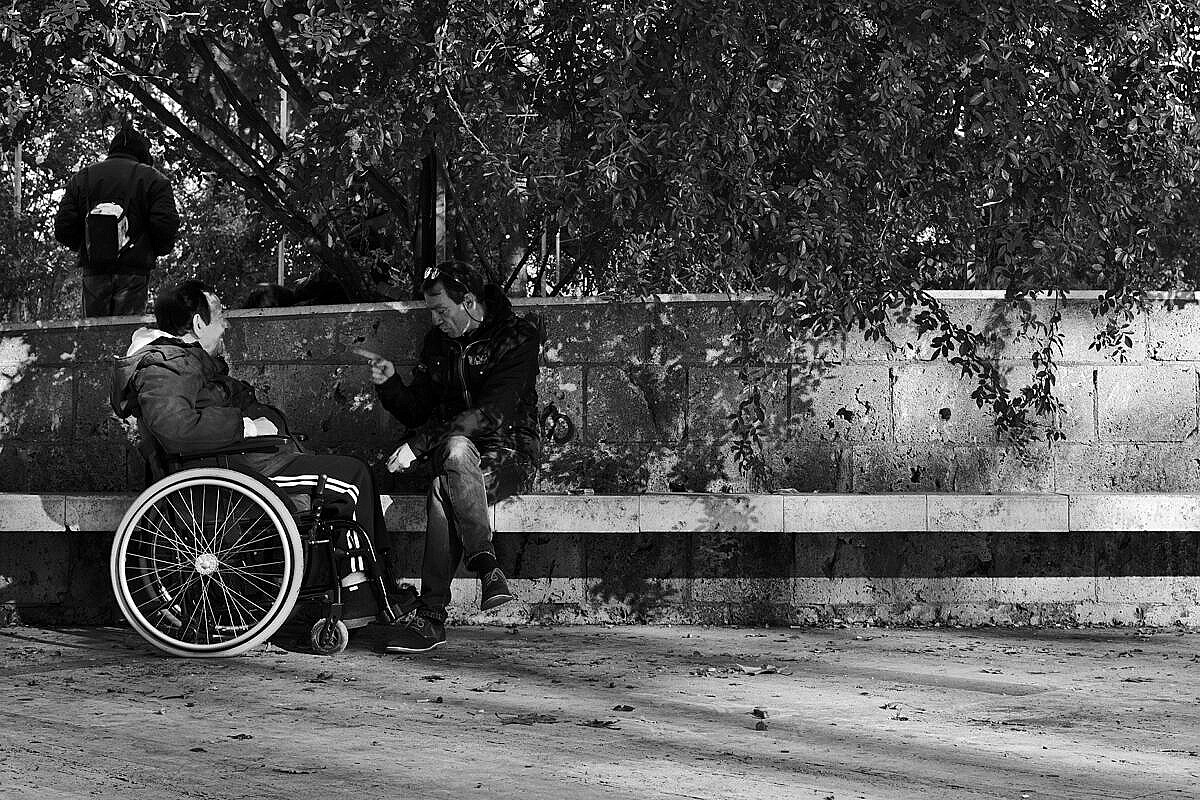Two people (one in a wheelchair) playing cards and chatting in a park on the Esquiline Hill in Rome