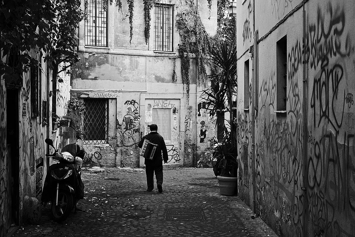 Street musician walking home alone through a picturesque alleyway in Trastevere in Rome.