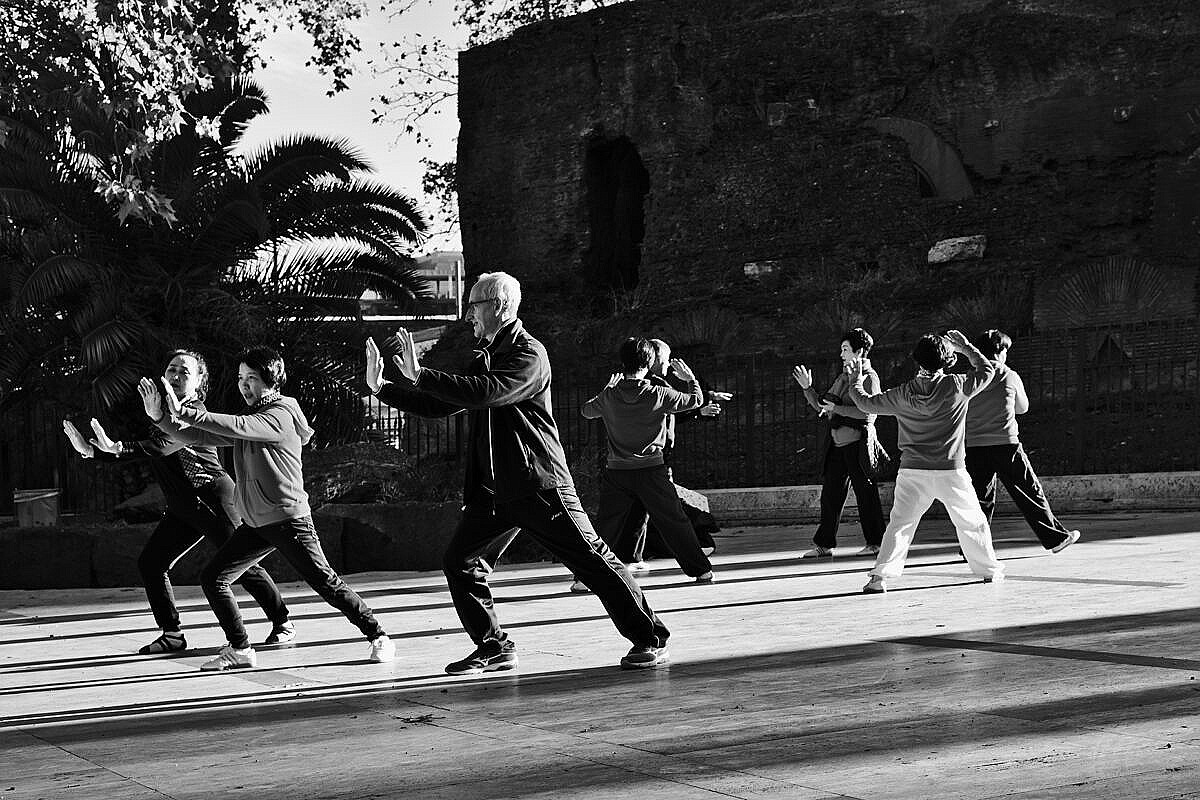 Group of people practising and teaching Tai Chi in a park on the Esquiline Hill in Rome.