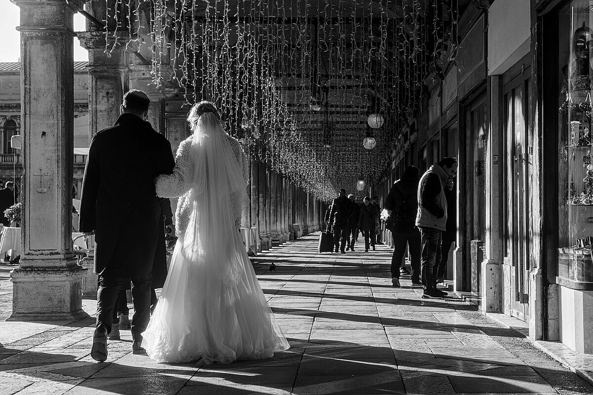 Couple of newlyweds walking under the procuratie in St. Mark's square