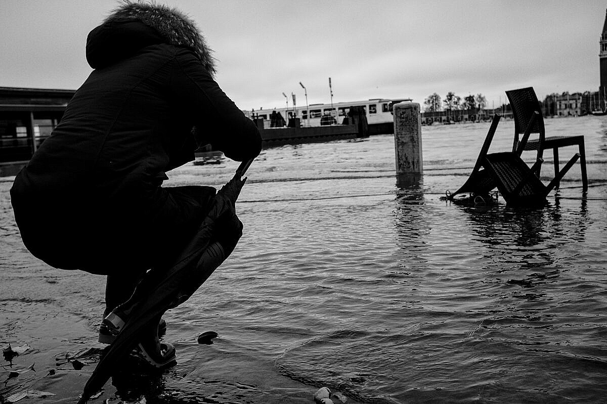 High tide - Venice under water - photographer at work