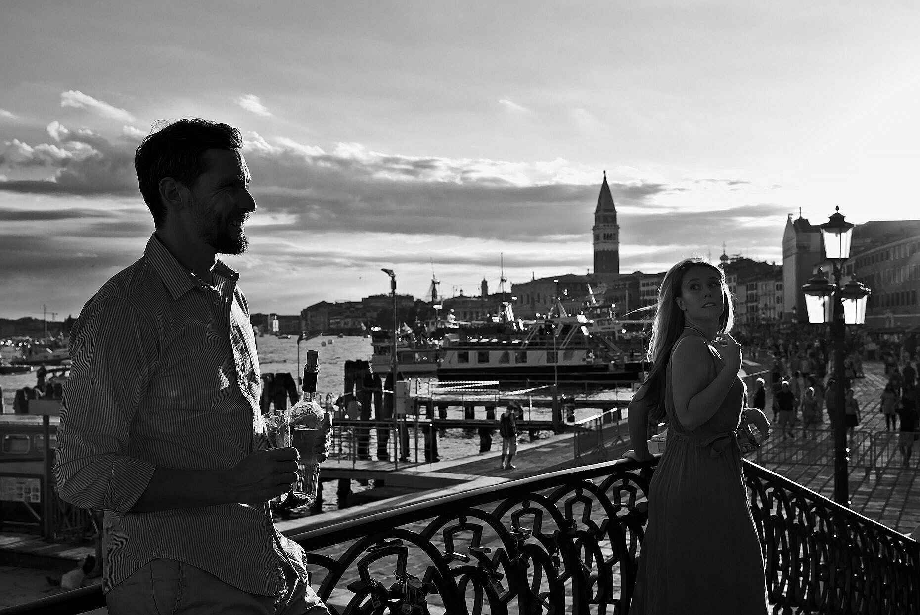 A woman glancing at a man on a bridge in Venice during the Redentore Feast in July
