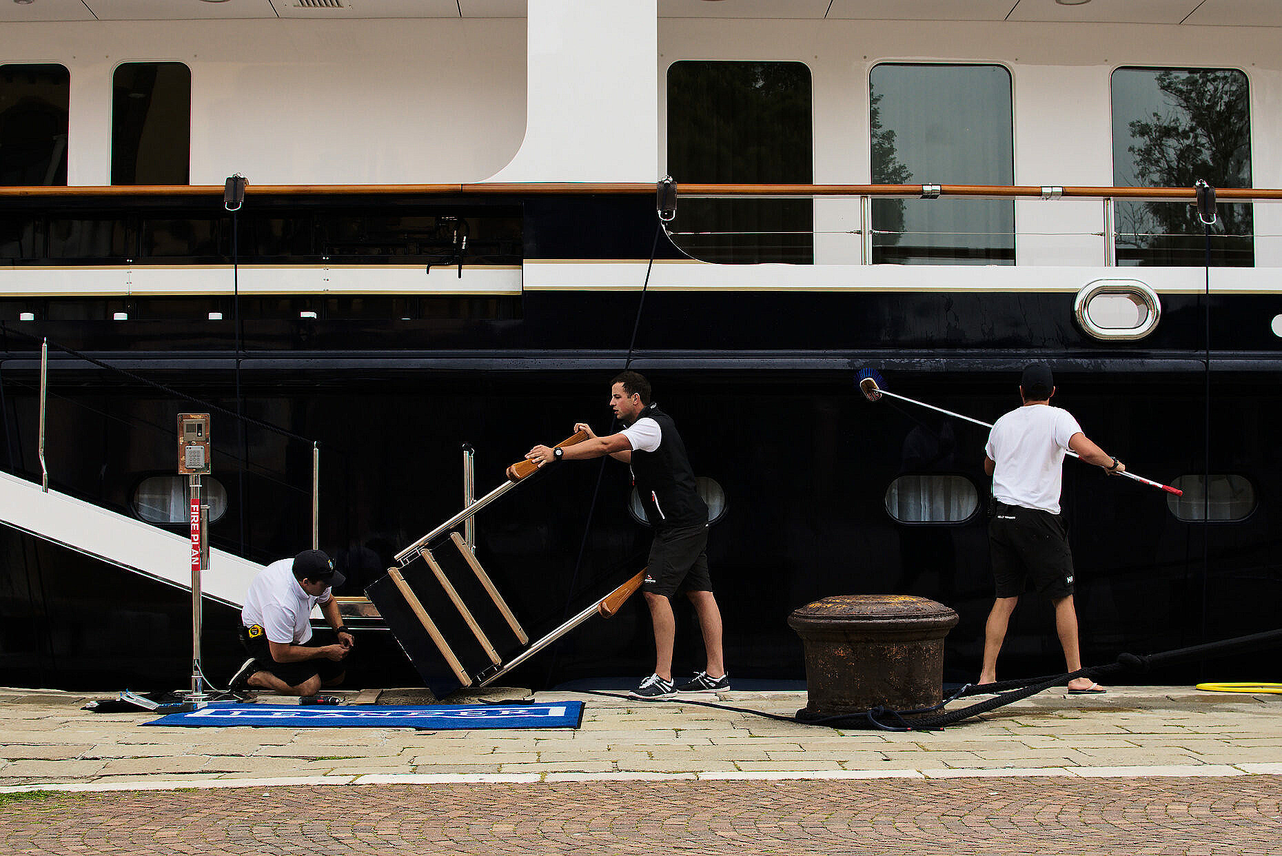 Three sailors occupied with maintenance and cleaning work on a yacht moored in Riva dei 7 martiri in Venice, Italy.