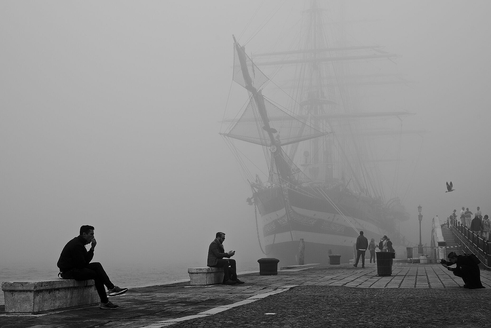 Tall ship Amerigo Vespucci in Venice on a foggy day, with people in the foreground