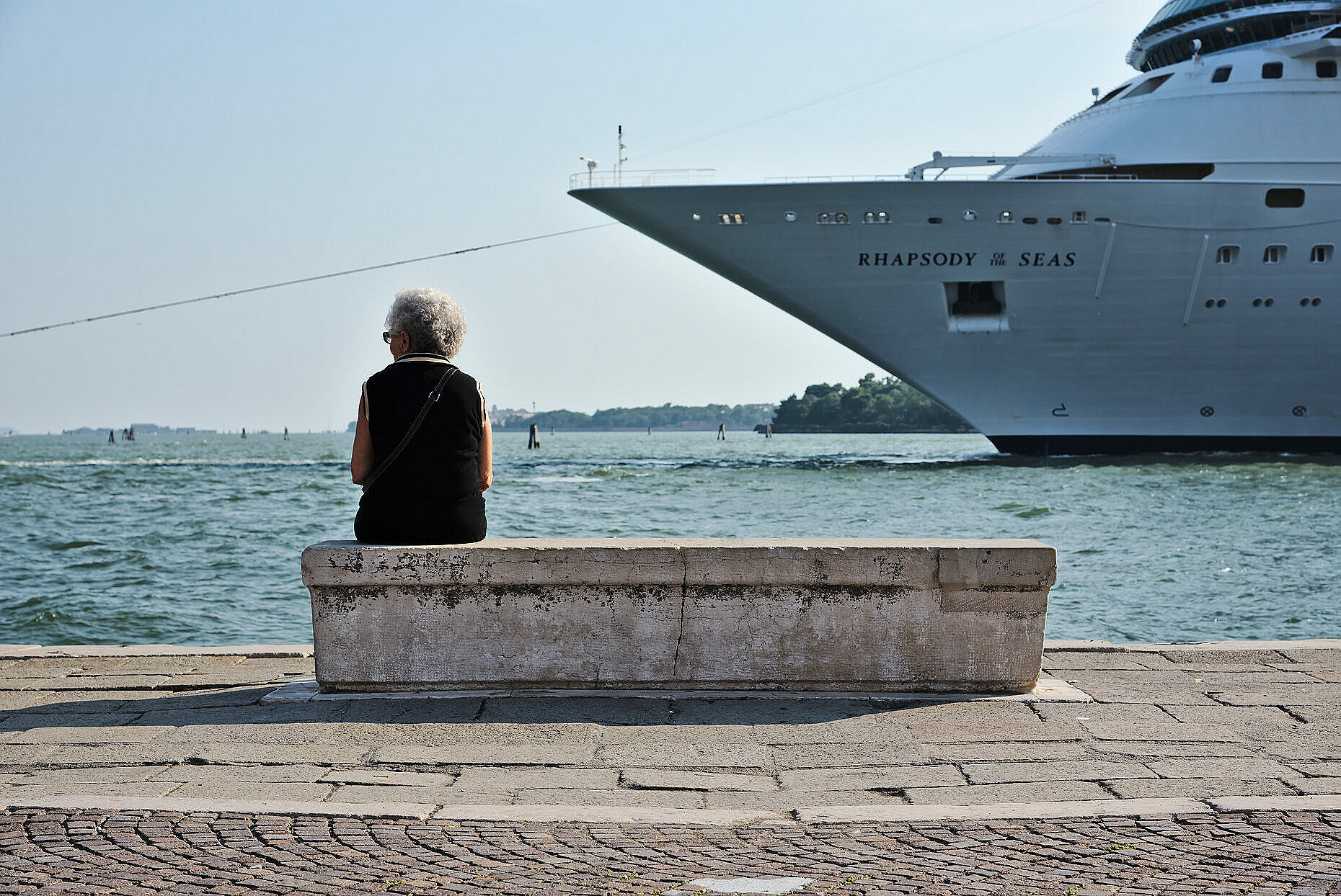 Woman sitting on bench in Venice, with a criuse ship approacing