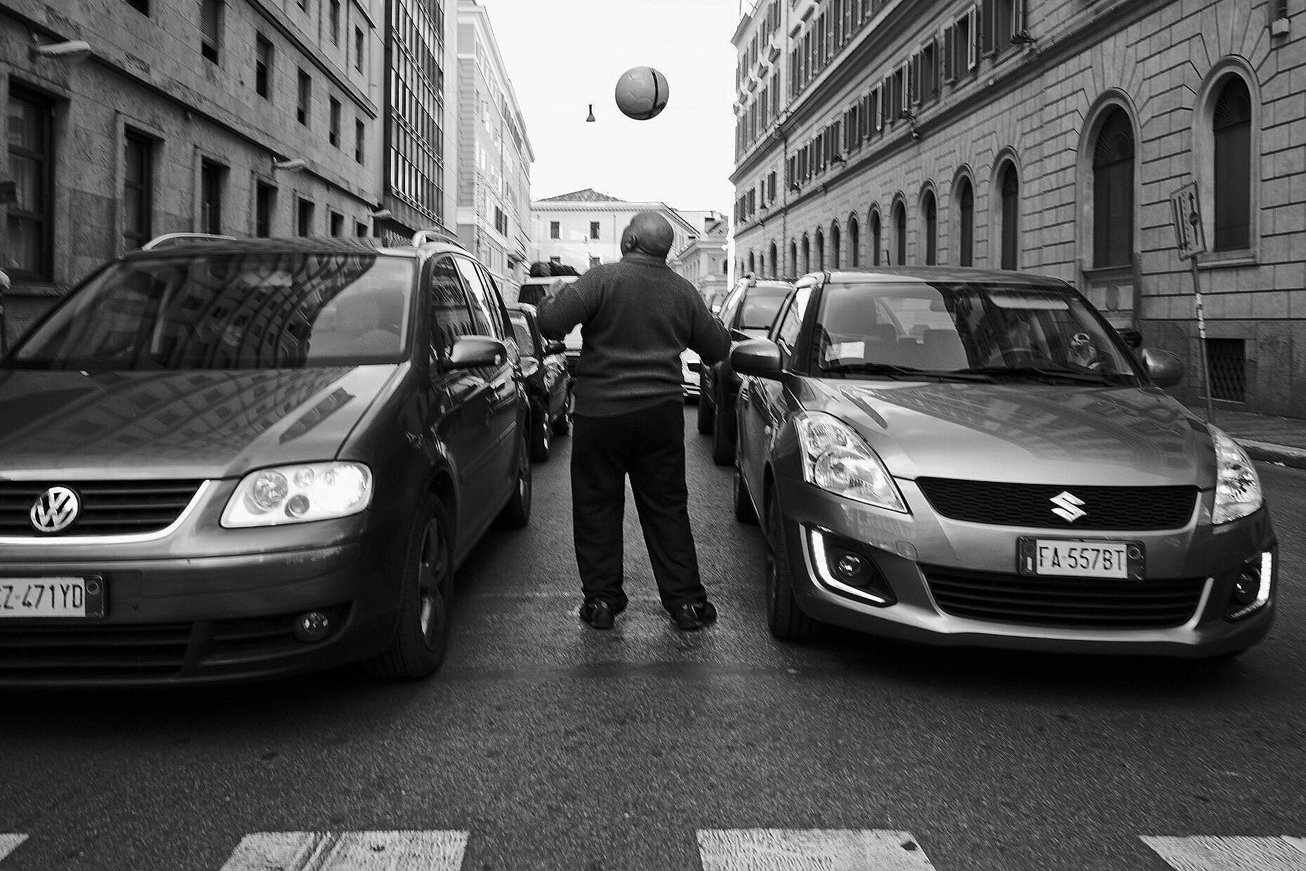 Man playing with a football between waiting cars in Rome.