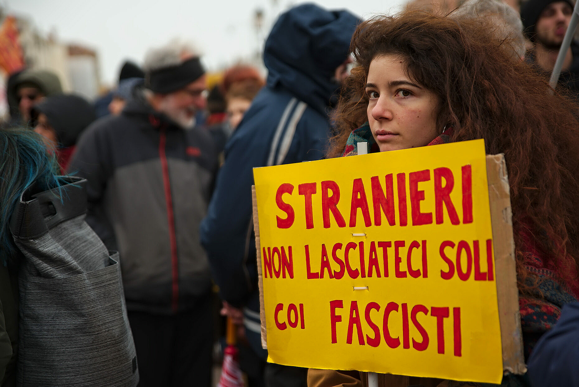 "Woman at an anti-fascist demonstration in Venice, with a sign saying ""Foreigners. Don't leave us alone with the fascists"""