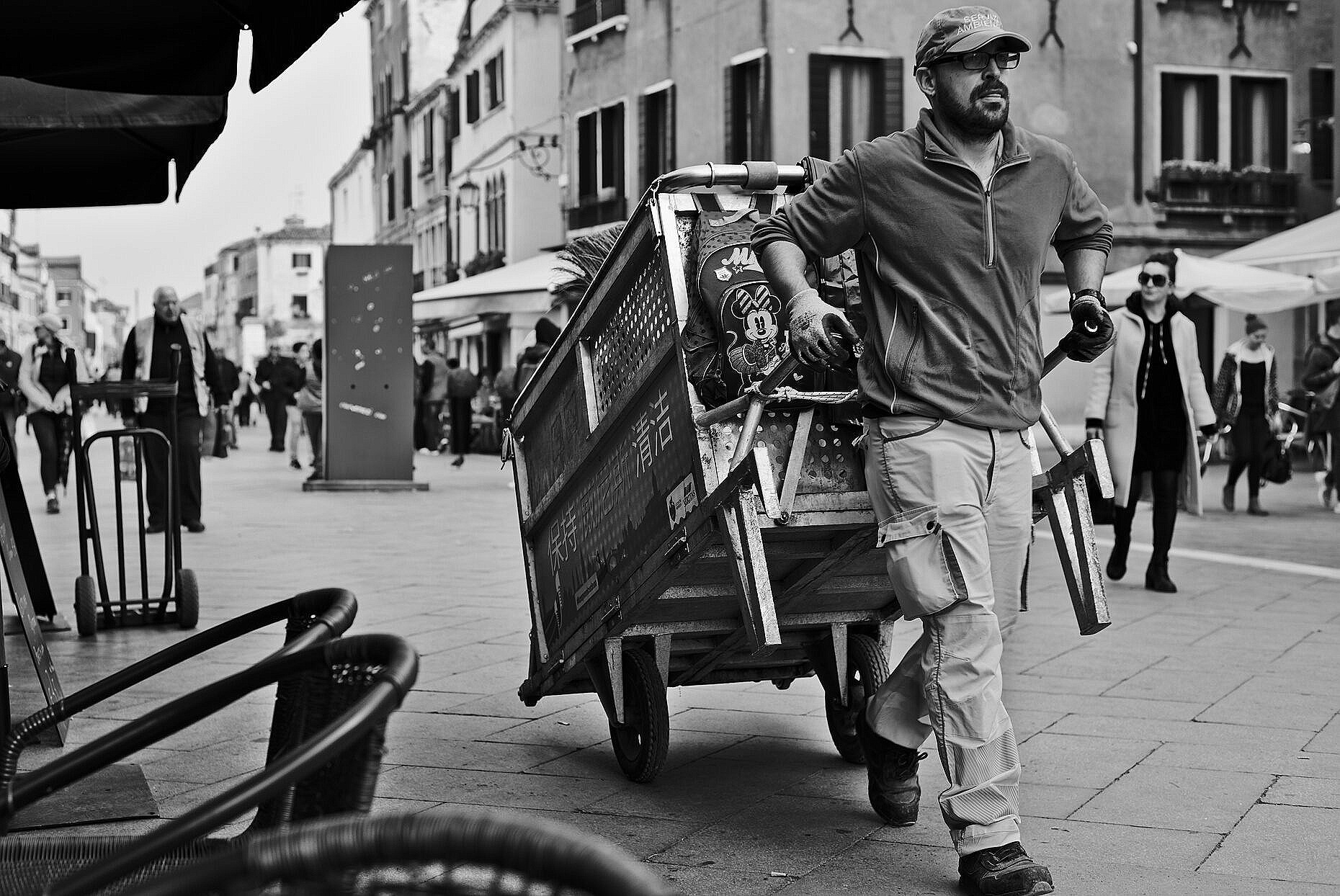Garbage collector in the Via Garibaldi with his hand drawn cart.