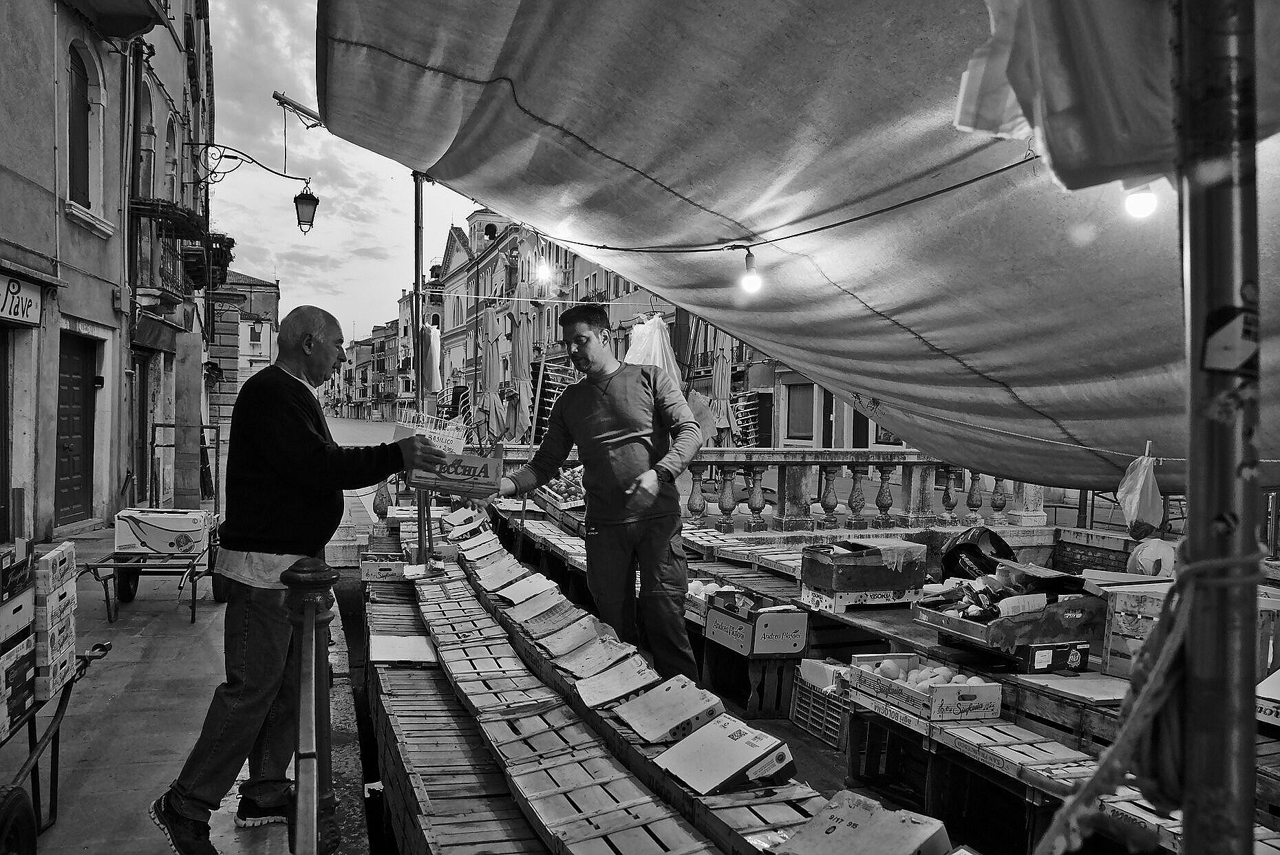 The greengrocers on a boat in Via Garibaldi getting ready in the early morning.