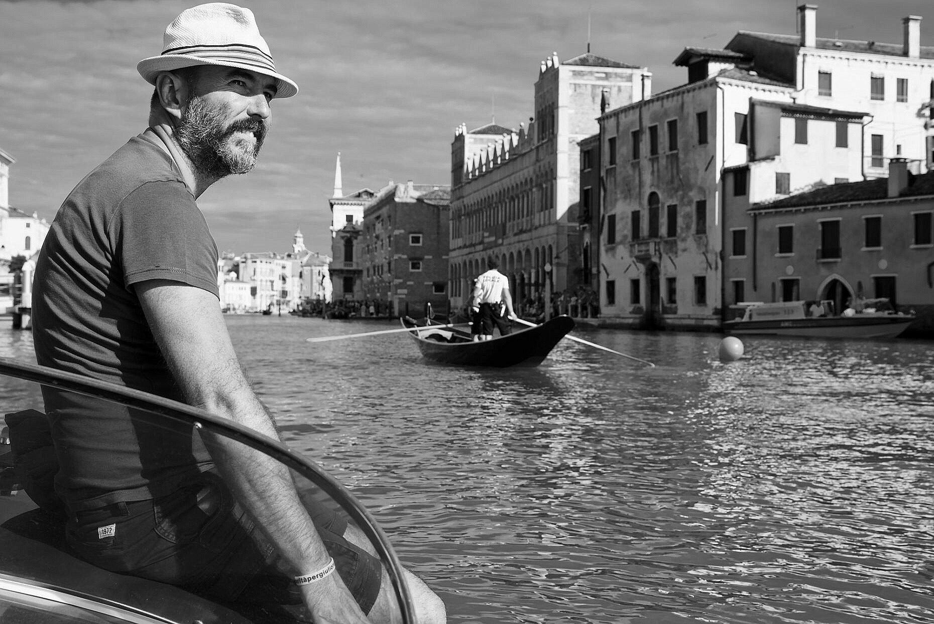 Francesco Penzo on the lookout for the Regata Storica 2018, sitting on the front of his motor boat on the Grand Canal while the local police is rowing past