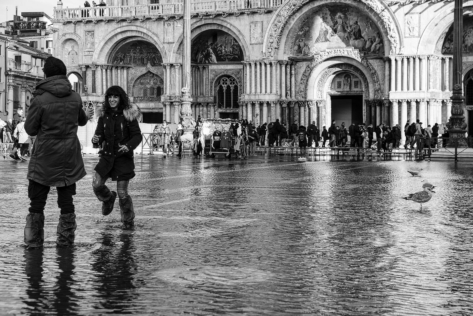 Young couple playing in the high water in St. Mark's square